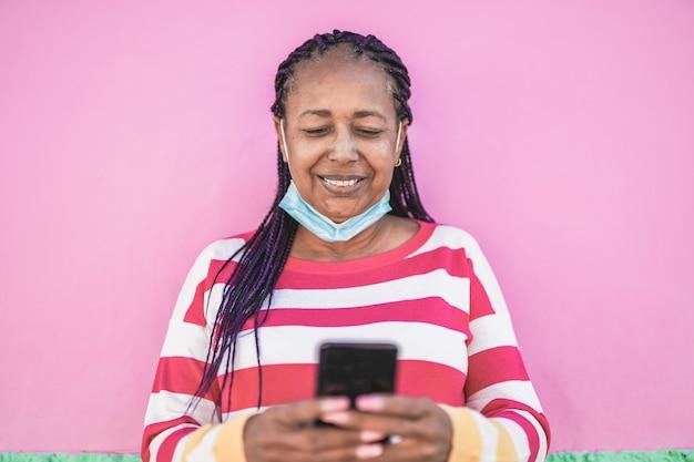 Пожилая африканская женщина использует мобильный телефон в городе, надевая защитную маску под подбородком из-за вспышки коронавируса