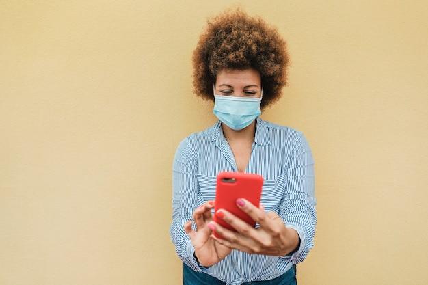 コロナウイルス予防のために顔面保護マスクを着用しながら携帯電話を使用している年配のアフリカの女性-顔にソフトフォーカス