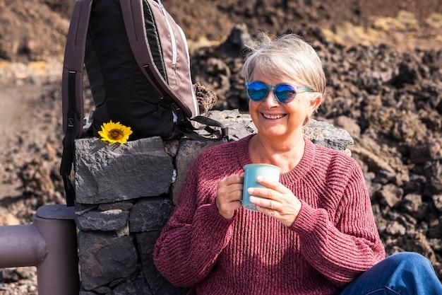 高齢者の魅力的な3歳の女性が笑顔でバックパックを持ってアウトドアバケーション旅行を楽しんで、社会からの自由と独立を感じてください-お茶を飲み、世界を訪れて幸せに過ごしましょう