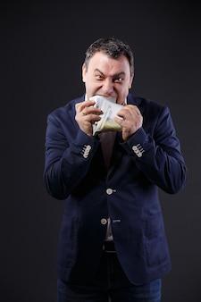 ユーロ紙幣を食べる年配のビジネスマン