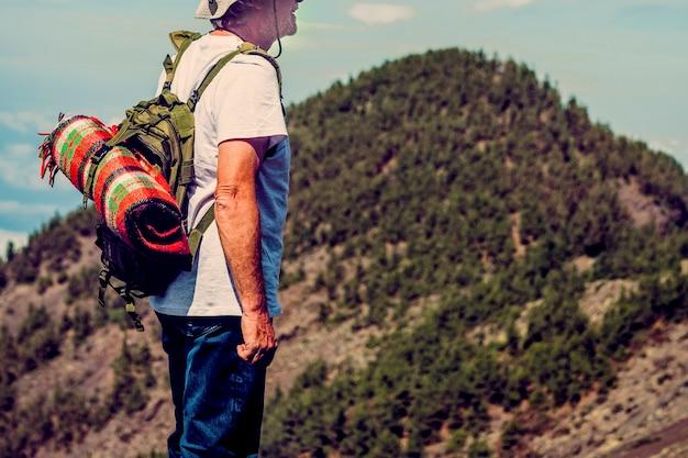冒険バックパックトレッキングツアーで山の頂上からの眺めを賞賛する年配の老人ハイカー-自然のアウトドアレジャー活動を楽しんでいるアクティブで健康的な成熟した引退した人々