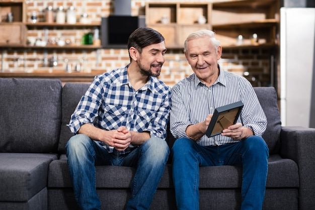 Senior aged man holding a photo frame while sitting on the sofa with his son
