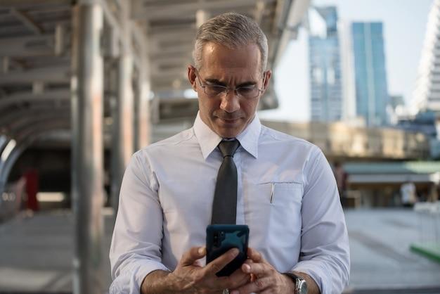 넥타이와 안경을 쓴 50대 미국 사업가는 현대 도시에서 스마트폰으로 사업 계획이나 회의 일정을 확인합니다. 중년의 ceo는 도시에서 운송하는 동안 일합니다.