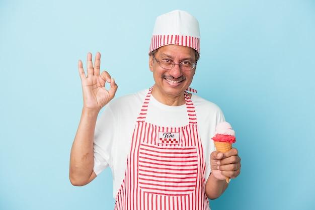 青い背景に分離されたアイスクリームを持っているシニアアメリカのアイスクリームの男は、明るく自信を持って大丈夫なジェスチャーを示しています。