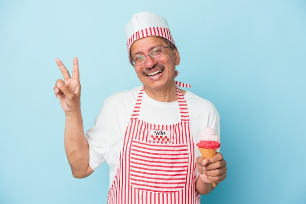 青い背景に分離されたアイスクリームを持っているシニアアメリカのアイスクリームの男は、指で平和のシンボルを示して楽しくてのんきです。