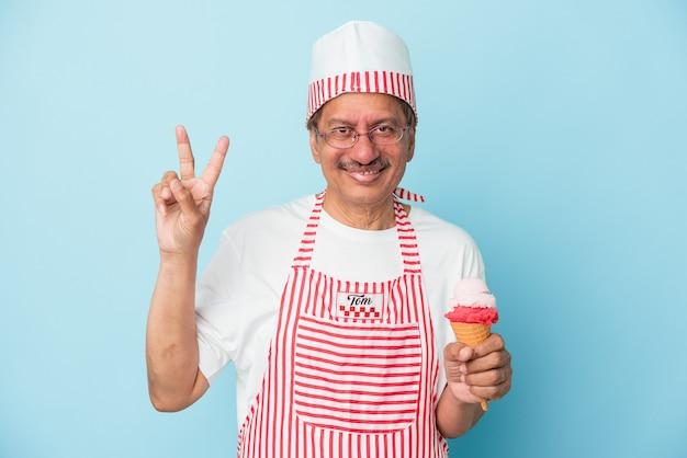 指で2番目を示す青い背景で隔離のアイスクリームを保持しているシニアアメリカのアイスクリームの男。