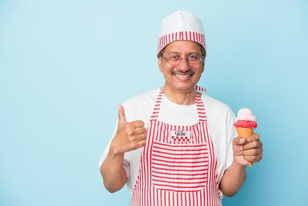 笑顔と親指を上げる青い背景で隔離のアイスクリームを保持しているシニアアメリカのアイスクリーム男