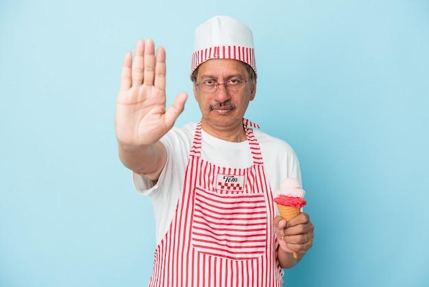 青い背景で隔離のアイスクリームを保持しているシニアアメリカのアイスクリームの男は、一時停止の標識を示す伸ばした手で立って、あなたを防ぎます。