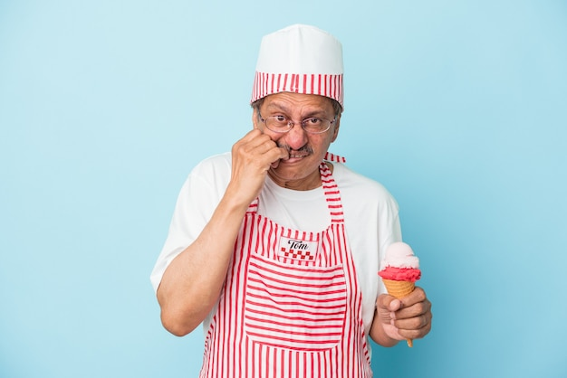 Senior american ice cream man holding an ice cream isolated on blue background biting fingernails, nervous and very anxious.