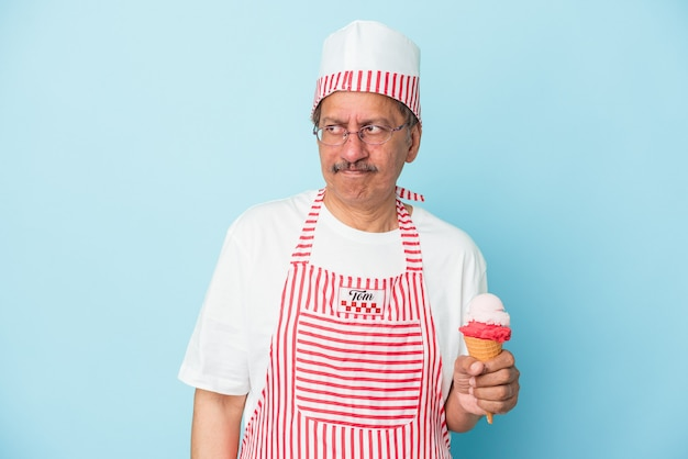 Senior american ice cream man holding an ice cream isolated on blue background confused, feels doubtful and unsure.