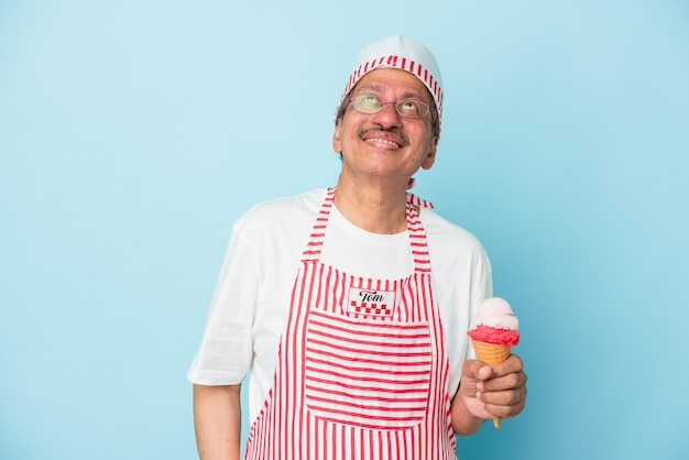 Senior american ice cream man holding an ice cream isolated on blue background dreaming of achieving goals and purposes