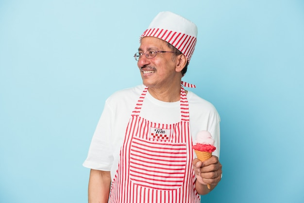 Senior american ice cream man holding an ice cream isolated on blue background looks aside smiling, cheerful and pleasant.