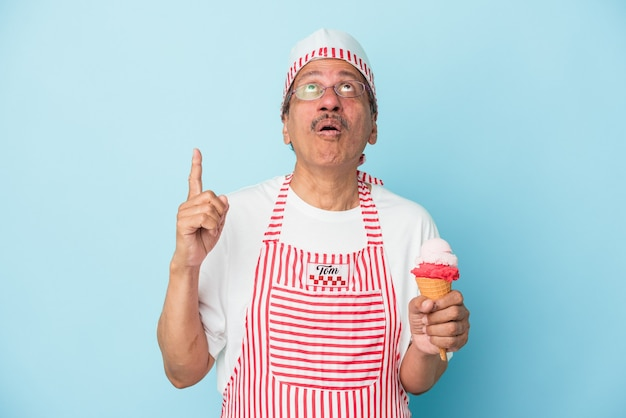 Senior american ice cream man holding an ice cream isolated on blue background pointing upside with opened mouth.