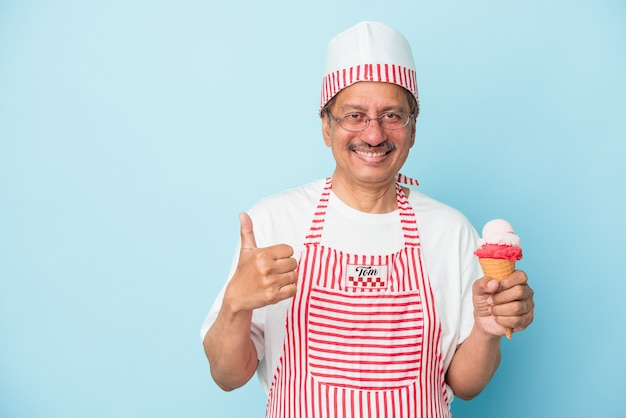 Senior american ice cream man holding an ice cream isolated on blue background smiling and raising thumb up