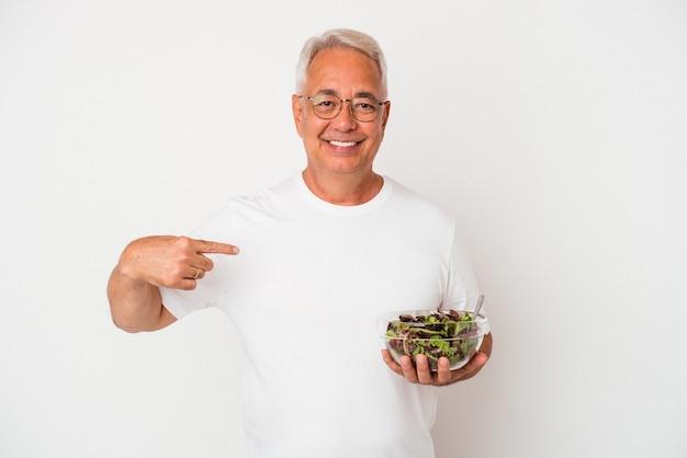 誇りと自信を持って、シャツのコピースペースを手で指している白い背景の人に分離されたサラダを食べる年配のアメリカ人