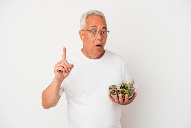 Senior american man eating salad isolated on white background having an idea, inspiration concept.