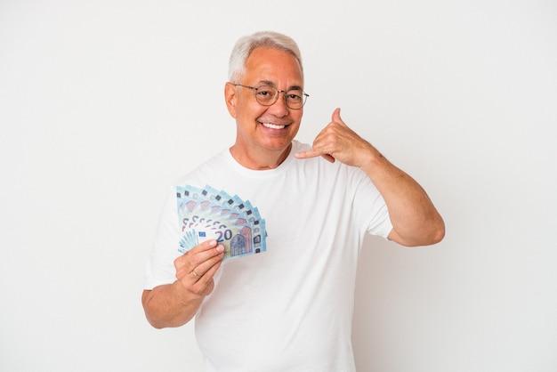 指で携帯電話の呼び出しジェスチャーを示す白い背景で隔離の請求書を保持している年配のアメリカ人男性。