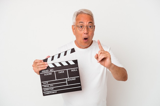 Senior american man holding a clapperboard isolated on white  background having an idea, inspiration concept.