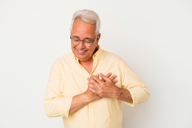 Senior american man isolated on white background has friendly expression, pressing palm to chest. love concept.