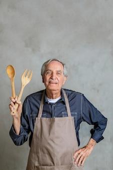 Старший американский мужчина в фартуке