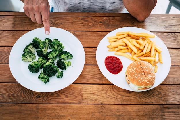 シニアと成熟した女性の手は、ハンバーガーとフライドチップを使った昼食ではなく、ブロッコリーを使った木製のテーブルの上の料理を示しています-ダイエットとダイエットと健康的なライフスタイル