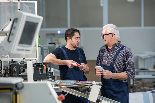 Старшие и молодые рабочие стоят у промышленного принтера и обсуждают печатные краски, наблюдая за цветовой палитрой