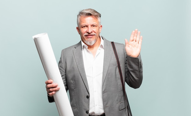Senior architect smiling happily and cheerfully, waving hand, welcoming and greeting you, or saying goodbye