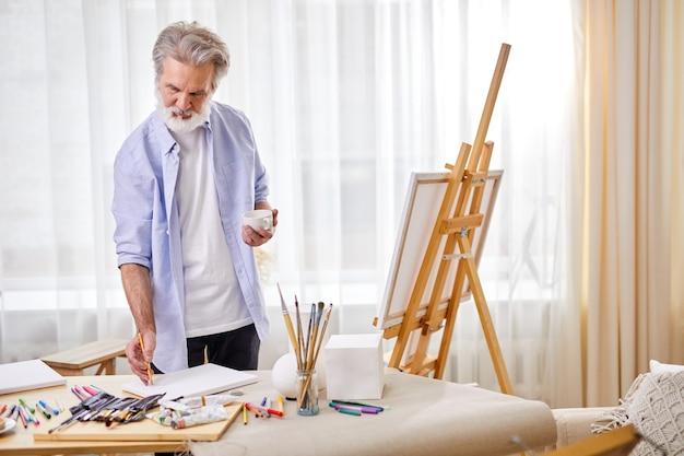 선임 예술가가 종이에 스케치를 그린 다음 캔버스에 서서 밝은 방에서 그림을 그립니다.