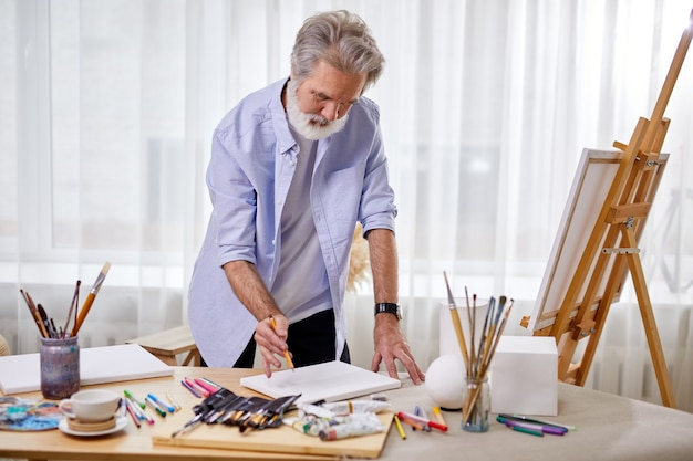 Senior artist draws a sketch on paper, and then on canvas, stands drawing, in light room