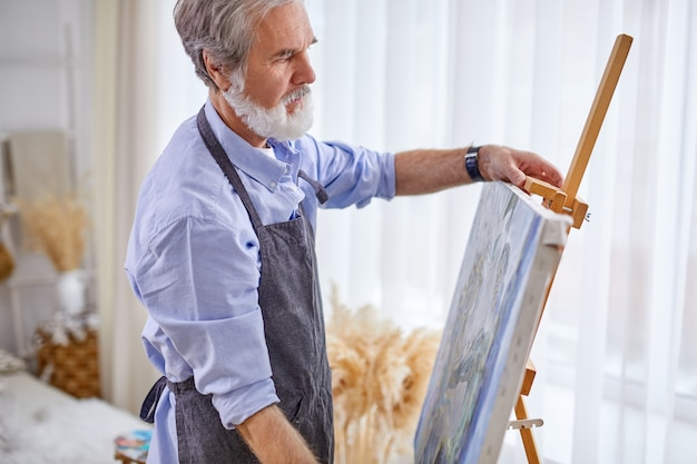 Senior artist remove the canvas from the easel, prepared painting in hands of skilled artist. in light room