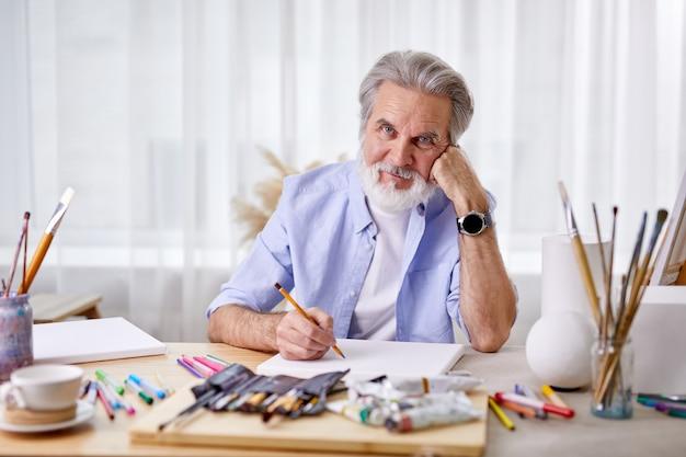 수석 아티스트 앉아 생각,. 성숙한 남자가 손에 기대어 그림에 종사하고 걸작을 만듭니다.