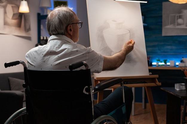 Senior artist with disability drawing vase design with pencil