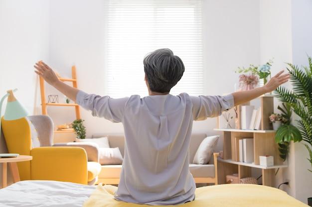 Старшая азиатская женщина сидит на кровати и разминается утром дома
