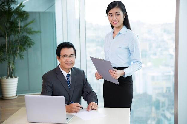 Senior asian boss signing document and secretary