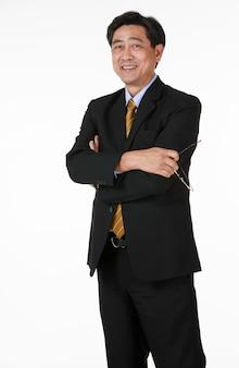 腕を組んで立っているアジアのシニアビジネスマン。眼鏡を外して笑顔でカメラを見てください。成功した銀行家、ビジネスマン、弁護士のキャラクター。よりリラックスして幸せそうな顔をします。