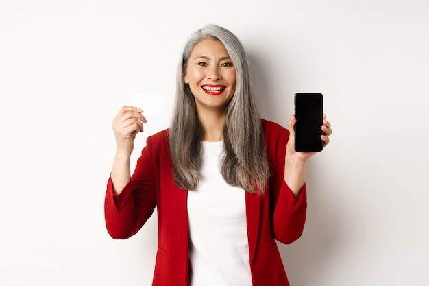플라스틱 신용 카드와 빈 스마트폰 화면을 보여주는 수석 아시아 여성, 카메라, 흰색 배경에 미소