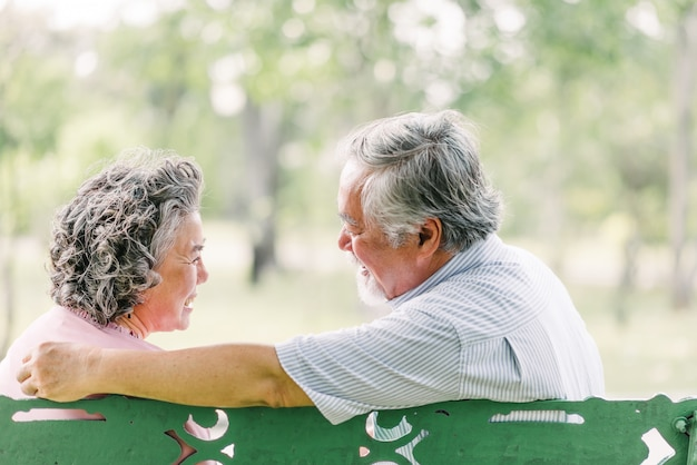 Senior asian couple enjoying together sitting on bench