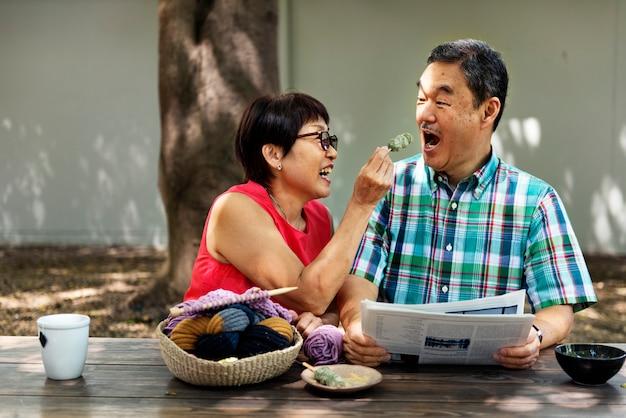 Senior asian couple garden feeding food concept