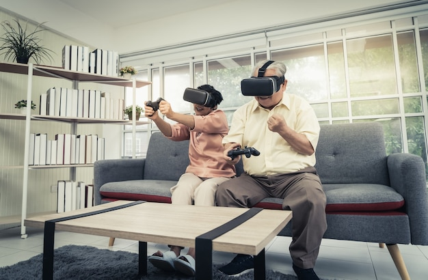 Senior asian couple is playing video game and wearing vr goggles with joypad for retirement technology lifestyle concept. Premium Photo