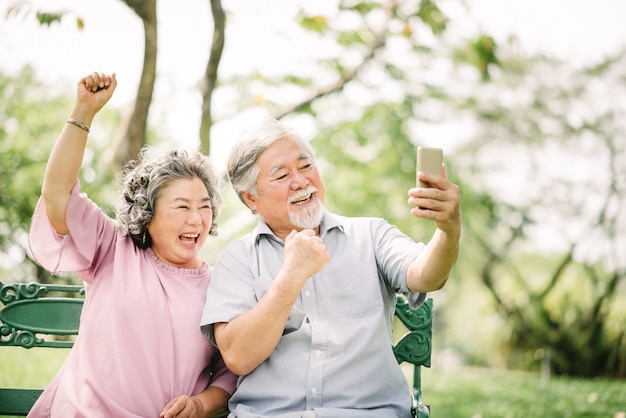 Senior asian couple laughing with smartphone
