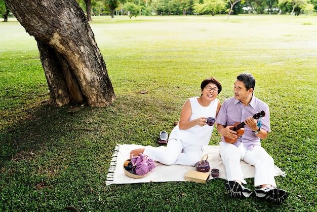 Senior asian couple picnic park playful concept