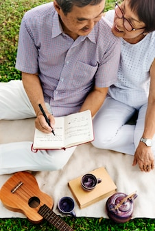 Senior asian couple picnic writing music ukulele concept
