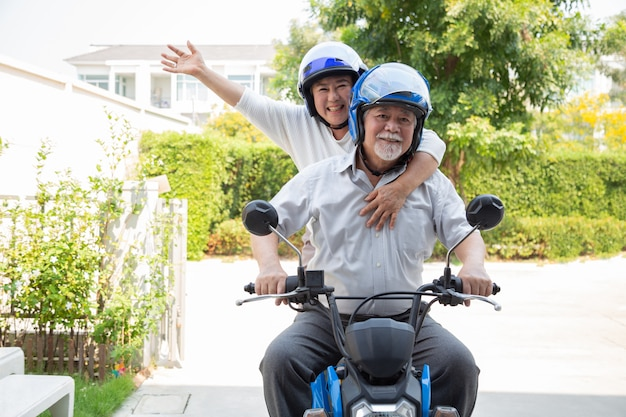 Senior asian couple riding motorcycle, happy active old age and lifestyle concept