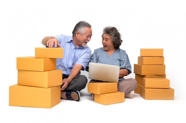 Senior asian couple startup small business freelance holding parcel box and computer laptop and sitting on floor, online marketing packing box delivery concept