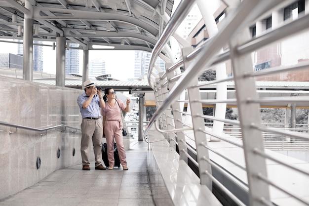 男性と一緒のアジアのシニアカップルは写真を撮るのをやめ、旅行の準備のために空港で笑顔で喜んでいます。旅行中のおばさんとおじさんの幸せは笑顔で旅をします。
