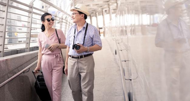 スーツケースをドラッグし、旅行の準備のために空港で笑顔で楽しく話している女性とアジアのシニアカップル。