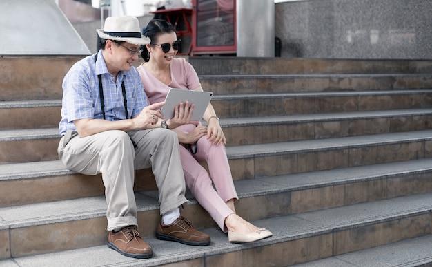 아시아의 노인 부부는 계단에 앉아 계획을 세우고 미소로 태블릿을 통해 여행 정보를 찾습니다. 수석 부부 여행 개념입니다. 이모와 삼촌은 관광 여행을 하는 동안 태블릿을 들고 계단에 앉아 있습니다.
