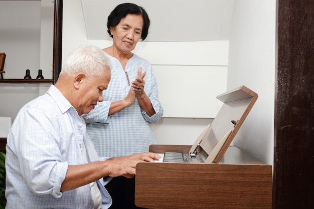 Senior asian elderly couple have fun playing the electric piano together. senior community concept
