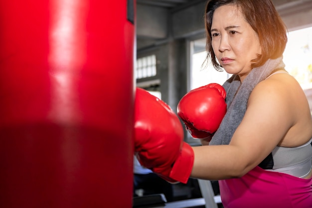 Senior asian fat woman training boxing at fitness gym.