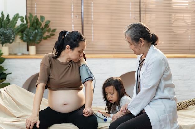 젊은 임산부 환자와 귀여운 소녀를 위한 수석 아시아 여성 의사 가정 방문